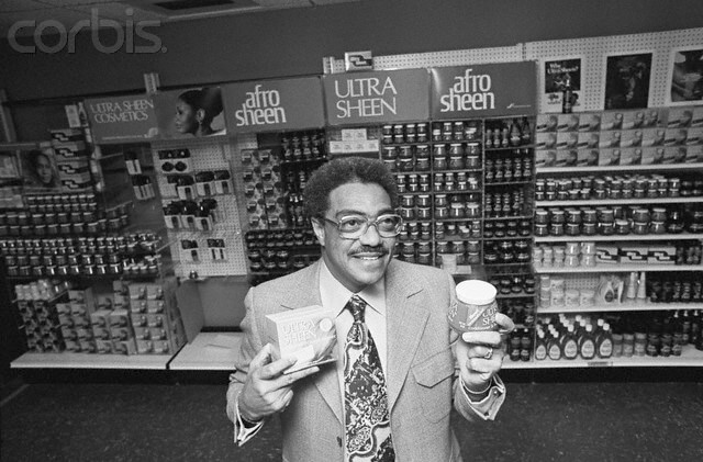 11 Jan 1976, Chicago, Illinois, USA --- Chicago: George E. Johnson a black entrepreneur with a high school education who parlayed a $250 investment into a company that grossed $39 million in sales, is seen in his office holding a few of the products made by Johnson Products Co., Inc. The firm is now the largest black manufacturing company in the world, with over 400 employees. --- Image by © Bettmann/CORBIS